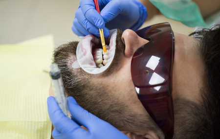 Smiling young man after visit dentist on bright blurred background. Dentist examining patients teeth in clinic. Beautiful european man smile with healthy teeth whitening.