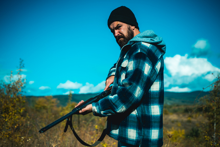 Hunter with shotgun gun on hunt. Hunting without borders. Clothes for the hunter. Close up Portrait of hamdsome Hunter.