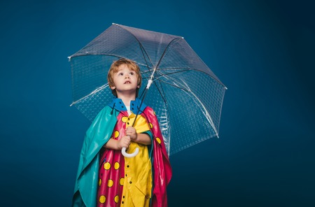 Cheerful boy in raincoat with colorful umbrella. Kid in rain. Cute little boy are preparing for autumn sunny day. Cute little child boy wearing in autumn clothes on autumn rain day.