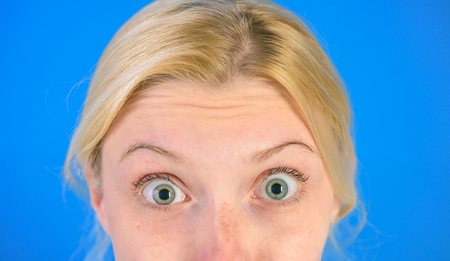 Woman wondering face show wrinkles on forehead. Skin care concept. Anti age skin cream. Cosmetics and aesthetic surgery. Girl with wrinkles on forehead close up. Signs of skin aging. First wrinkles Stock Photo
