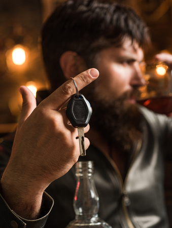 Man with beard holds glass brandy. Macho drinking. Confident man with car keys in his hand. Do not drink and drive Cropped image of drunk man talking car keys. Stock Photo