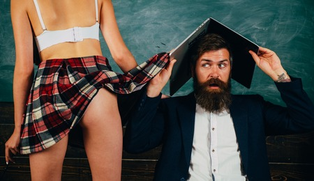 Hombre experimentado profesor barbudo y nalgas femeninas seductoras. Aprendiendo el cuerpo femenino. Concepto de vida sexual. Piernas de estudiante deseables. Juego de rol sexual. Educación sexual. Video de la computadora portátil de chico Foto de archivo