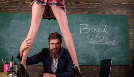 Man bearded teacher and female mini skirt sexy legs. Erotic lesson concept. Subordinate and submission. Desirable sexy student. Sex education. Sexy girl hold whip. Curious sexy learner. Sex role game 版權商用圖片