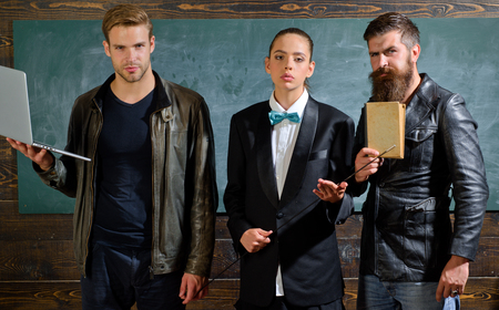 Diversity concept. School staff. People with laptop book stand in school classroom. School teachers. Bearded man masculine girl and handsome guy school colleagues. Teaching and education occupation