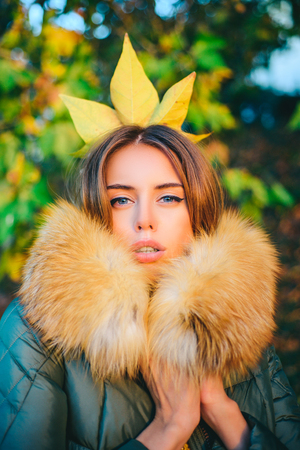 Autumn princess. Fall season outfit. Modern fashion outfit. Gorgeous pretty woman in furry coat fallen leaf on head as crown. Trendy outfit. Her confidence is stunning. Woman feeling as autumn queen
