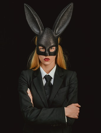 Portrait of a happy woman in bunny ears winking. Sexy blonde girl with lace bunny ears. Easter dinner menu. Sexy woman wearing a mask Easter bunny and looks very sensually.
