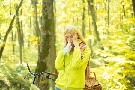 Runny nose remedies. Woman handkerchief sneezing because of allergy. Blonde allergic reaction relax forest. Girl bicycle in nature. Woman bicycle autumn forest suffers from allergy. Seasonal allergy Stock fotó - 121900395
