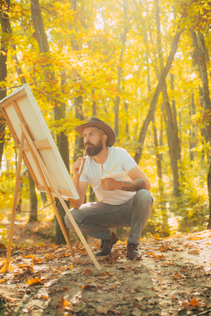 Painter artist forest. Art concept. Painting in nature. Start new picture. Painter with easel and canvas. Bearded man painter looking for inspiration autumn nature. Relax and hobby. Drawing from life
