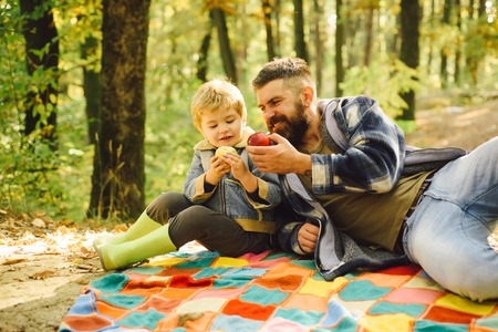 Forest picnic hiking. Healthy lifestyle. Nature picnic. Healthy snack. Vitamin charge. Family picnic. Hipster bearded dad with son spend time in forest. Brutal bearded man and little boy eat apples 版權商用圖片