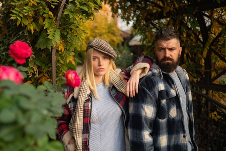 Stylist service. Lumberjack style. Couple wear checkered clothes nature background. Man bearded hipster and girl wear kepi hat. Checkered style. Couple handsome bearded hipster and fashion girl