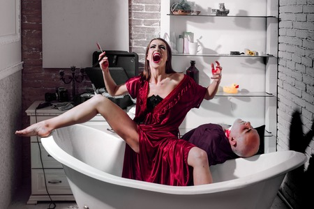 Killer lover. Wife killed husband. Criminals or murderers with a knife in the blood. Dead body lying on the bath. Crime scene. Stockfoto