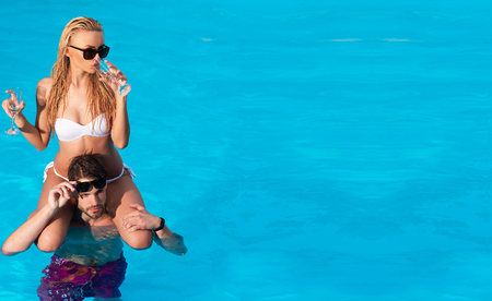 Ibiza. Concept about party and music. Beautiful young women and stylish man drinking cocktails on beach. Happy honeymoon vacation at Paradise. Young couple active leisure swimming pool concept. Stock Photo