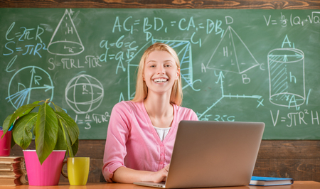 Confident woman with laptop working online teacher. Modern education. Back to school. Remote education. Student adorable blonde girl classroom chalkboard background. STEM concept. Formal education
