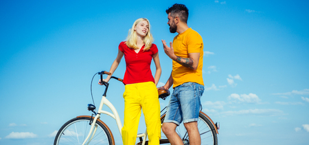 Romantic young couple. Beautiful summer day. Retirement. Adventure and vacations concept. Summer woman with retro bike on blue sky background.