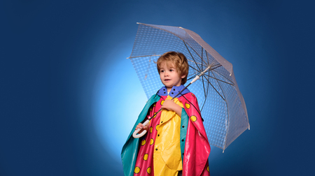 Child advertise your product and services. Cheerful boy in raincoat with colorful umbrella. Autumn concept. Cute little child boy are getting ready for autumn. Raining kids.