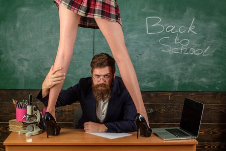 Juego de rol sexual. Maestro barbudo hombre y piernas de minifalda femenina. Concepto de lección erótica. Subordinado y sumisión. Estudiante deseable. Educación sexual. Chica sexy mantenga el látigo. Aprendiz curioso