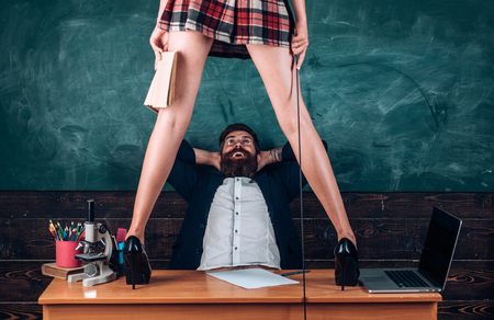 Sex role game. Man bearded teacher and female mini skirt sexy legs. Learning sexy female body. Domination and submission. Desirable sexy student with whip high heels stand on table. Sex education