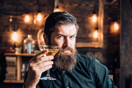 Retro bar. Bearded man sitting at bar. Handsome man drinking olcohol while sitting at the bar.