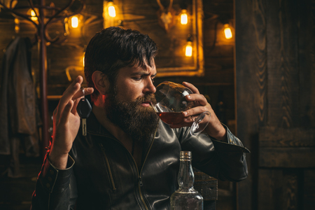 Man with beard holds glass brandy. Macho drinking. Confident man with car keys in his hand.