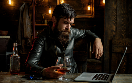 Portrait of a handsome man with beard. Brutality and masculine concept. Barbershop, shaving.Macho is drinking by his laptop. Concentrated.