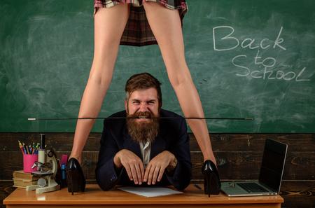 Concepto de lección erótica. Subordinado y sumisión. Estudiante deseable. Educación sexual para todas las edades. Aprendiz curioso. Juego de rol sexual. Maestro barbudo hombre y piernas de minifalda femenina Foto de archivo