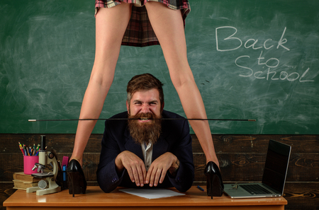 Erotic lesson concept. Subordinate and submission. Desirable student. Sex education for all ages. Curious learner. Sex role game. Man bearded teacher and female mini skirt legs