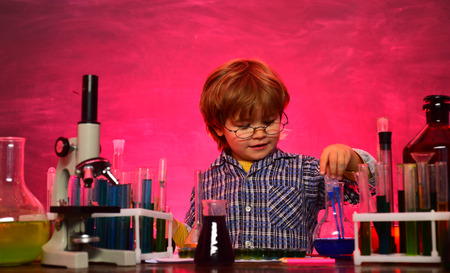 Child in the class room with blackboard on background. schoolboy. They carried out a new experiment in chemistry. Knowledge day. Home schooling. School concept 版權商用圖片