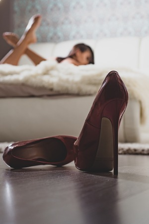 High heels in front of female bedroom defocused. Sexy erotic woman relaxing on bed. Attractive female relax. Erotic massage. Escort service. Desire concept. Erotic attribute. Foot fetish concept Banque d'images