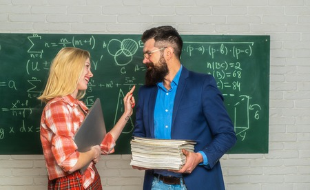Bearded tutor helping his student. Teacher couple. Teacher helping his students with math or mathematics on education class.