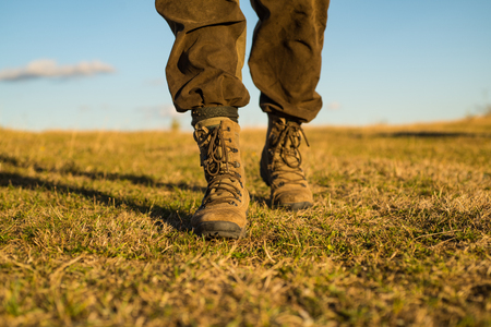 travel adventure. future. military shoes. male feet in green boots. hynter searching for victim in grass field. going to success. freedom. soldier uniform. step up. walking. hiking and camping