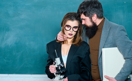 Sexy female student pointing at chalkboard. Workplace romance of handsome man and sexy woman in university. Friendship and good warm relations concept. Love romance seduction dating.