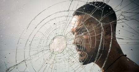 crack. macho man behind crushed glass. anger. destruction. crush test. theft. emotional discharge. bullet hole in glass. broken glass because of hit. sexy hispanic man broken mirror. crack in glass
