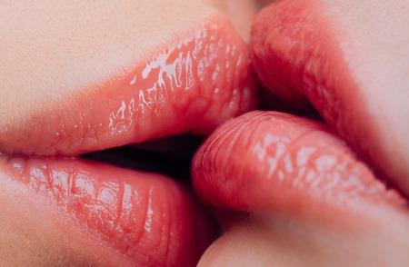 Lesbischer Kuss. Sinnliches nasses weibliches Lippenküssen. Lesbische Freuden. Orales Vergnügen. Paar Mädchen, die Lippen hautnah küssen. Küssende Aktivität mit sinnlicher Berührung. Heißes Vorspiel. Lippenpflege. Aufklärungsunterricht