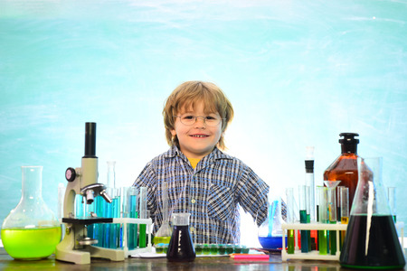 Back to school and home schooling. Cheerful smiling little boy having fun against blue wall. Back to school. First grade. Biology experiments with microscope
