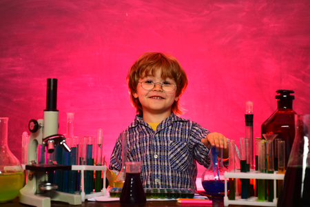 Little kids scientist earning chemistry in school lab. Science. Happy little scientist making experiment with test tube. schoolchild