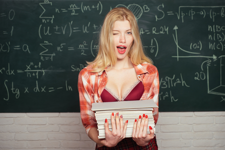 Back to, school. Young sensual student near chalkboard in school classroom. Tutor. First school day. First school day. Emotional sensual woman student screaming on classroom chalkboard background. Foto de archivo