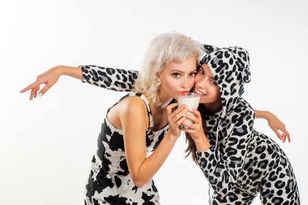 Dairy is a building block of life. Pretty girls on dairy diet drinking milk together. Fashionable dairy food consumers in spotted cow design clothes. Consumption of dairy products Archivio Fotografico