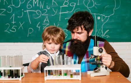 Teacher and schoolboy using microscope in class. Wunderkind. Science and education concept. Learning at home. Concept of education and teaching. Knowledge day. Teacher
