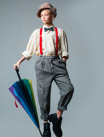 suspender and bow tie. old fashioned child in checkered beret. retro fashion model. vintage charleston party. vintage english style. teen girl in retro suit with umbrella. jazz step fashion Stockfoto