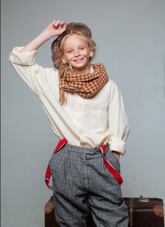 adventure. teen girl in retro male suit. street kid with dirty face. vintage english style. Travel with old suitcase. Homelss. old fashioned child in beret. retro fashion model. Vintage suspender