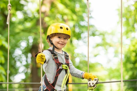 Happy child boy calling while climbing high tree and ropes. Portrait of a beautiful kid on a rope park among trees. Small boy enjoy childhood years. Stock Photo