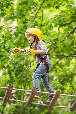 Little child climbing in adventure activity park with helmet and safety equipment. Climber child on training. Rope park - climbing center