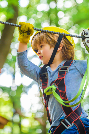 Cute child in climbing safety equipment in a tree house or in a rope park climbs the rope. Happy little child climbing on a rope playground outdoor.