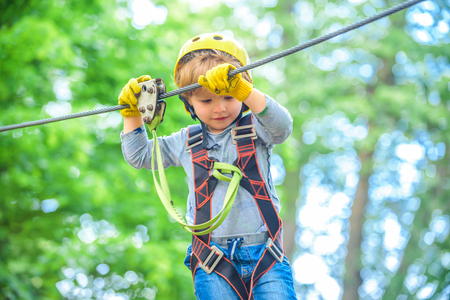 Child boy having fun at adventure park. Happy child climbing in the trees. Happy Little child climbing a tree. Balance beam and rope bridges.