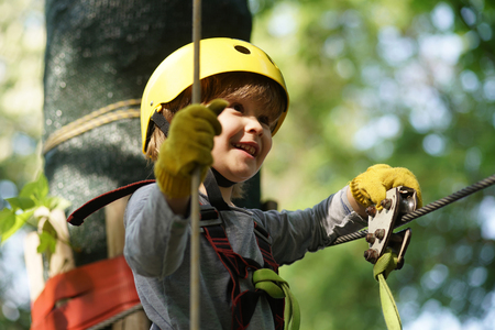 Climber child on training. Cute little boy in climbing safety equipment in a tree house or in a rope park climbs the rope. Safe Climbing extreme sport with helmet