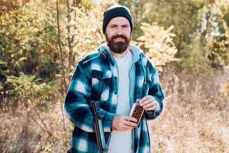 Hunter with shotgun gun on hunt. Close up Portrait of hamdsome Hunter.