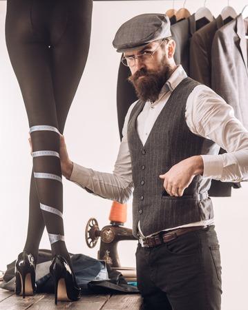Wir lieben Designer. Damenschneider, die Designer-Kollektion von Modekleidern machen. Bärtiger Mann, der weibliche Kleidung im Designergeschäft schneidert. Modedesigner oder Couturier bei der Arbeit