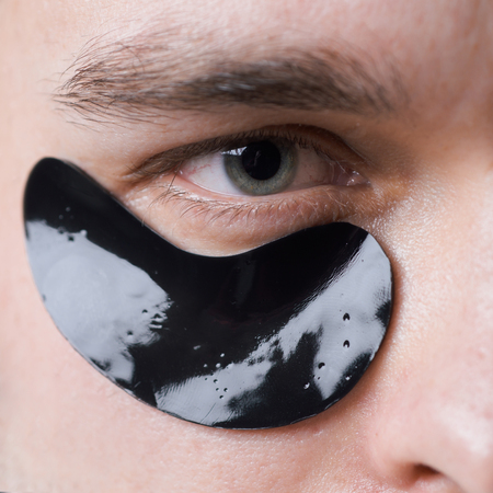 Black pearl extract. Skin care. Minimizes puffiness and reduce dark circles. Eye patches for men. Man with black eye patches close up. Metrosexual concept. Focused treatments for under eye area Stock Photo