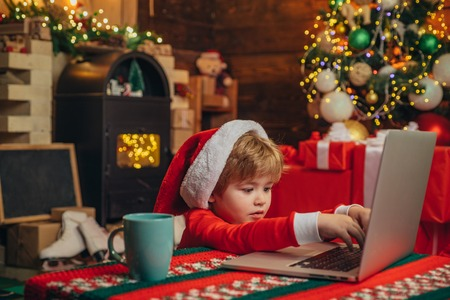Santa little helper. Little boy santa hat and costume having fun. Boy child with laptop near christmas tree. Stock Photo