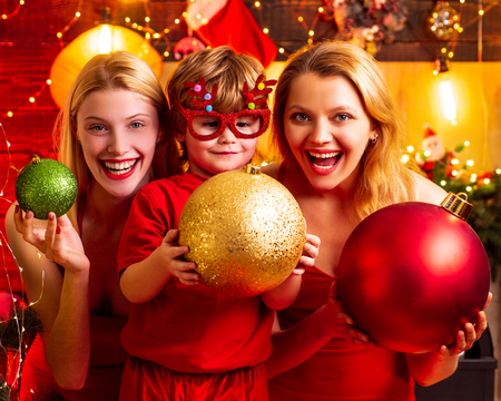 Christmas family fun. Christmas party. Women red dresses festive mood celebrate Christmas with little cute baby. Family bonds. Love peace joy wishes. Kid boy with mom or aunts sisters having fun Reklamní fotografie - 122566996